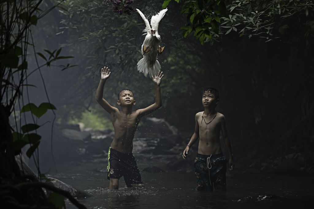 Photo and caption by sarah woutersTwo boys are trying to catch a duck at the stream of the waterfall. Nong Khai Province, Thailand.