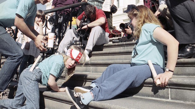 A group of handicapped people led by 8-year-old Jennifer Keelan, left, crawl up the steps of the U.S. Capitol in Washington, March 12, 1990, to draw support for a key bill now pending in the House that would extend civil rights to disabled persons. The group of about 1,000 people or rode in wheelchairs down Pennsylvania Avenue from the White House to the Capitol. (AP Photo/Jeff Markowitz)