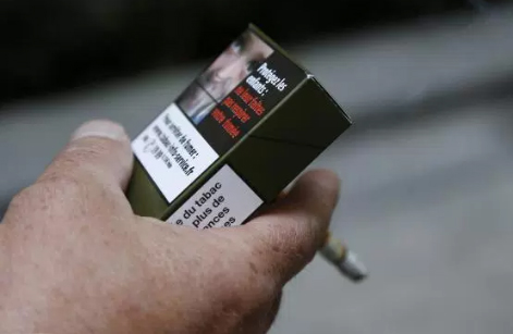 """A man smokes a cigarette in Paris, holding a sample of a """"plain cigarette packaging"""" cigarette box (Getty Images)"""